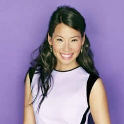 Lucy Liu in white dress smiling with a purple background drop