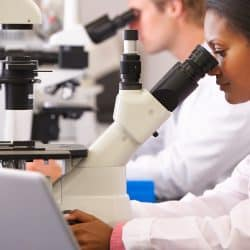 black woman in lab coat looking through micoscope