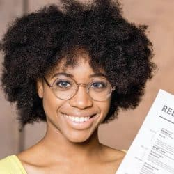 woman holding her resume in her hand smiling