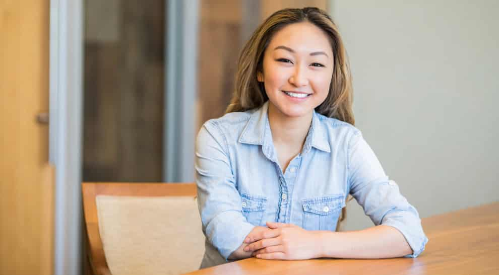 professional woman sitting at desk in office smiling