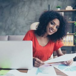 Women sitting behind office desk reviewing a paper and smiling