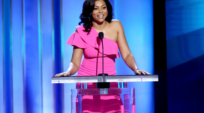 Taraji stands behind a podium while speaking to an audience