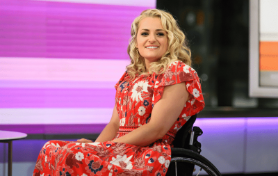 Ali Stroker sits on stage in a wheelchair smiling wearing a pink and red flroral dress