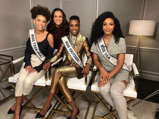 Black women beauth pageant winners seated together with their sashes on