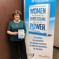 Nancy Parsons posing in front of her book promo poster