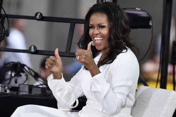 Michelle Obama dresses in all white giving a thumbs up sign