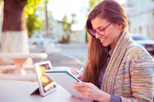 young woman writing notes about resume on notepad