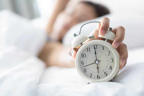 Closeup woman sleeping on bed and hand holding alarm on clock