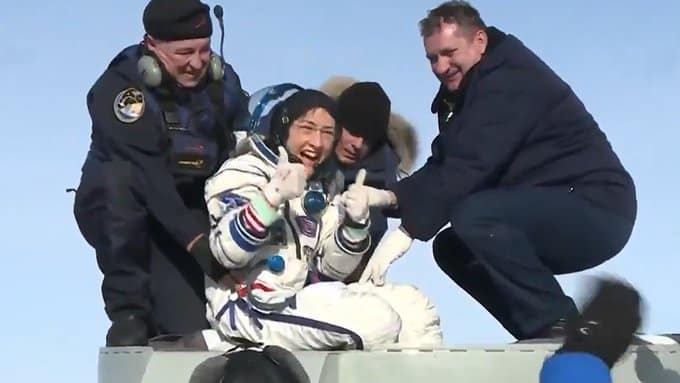 Chrsitina Koch touches down on earth wearing her spacesuit and smiling while two men help her balance