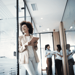 Black female business owner standing in building looking out large window