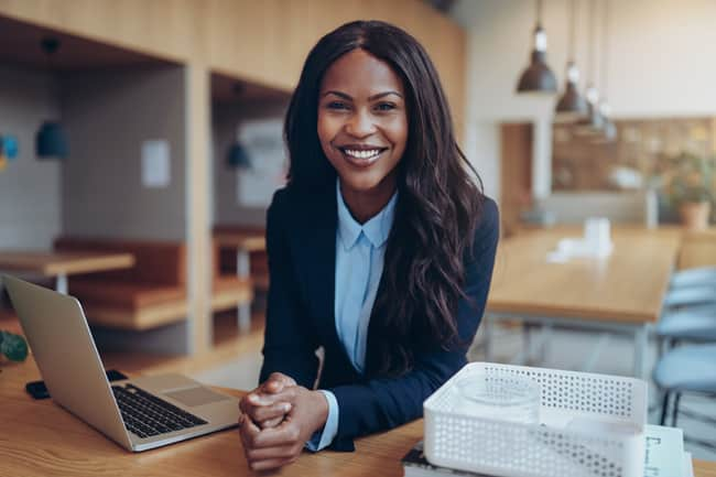 Smiling young African American businesswoman leaning on a table in her office