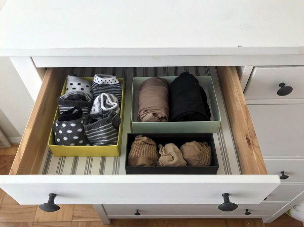 Socks and tights are seen arranged in a drawer in small boxes as recommended by Kondo
