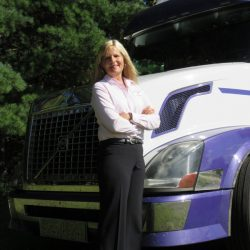 Ellen is standing in front of a semi-truck outside smiling confidently