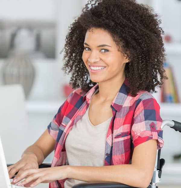 cheerful disabled young woman using laptop doing remote work from home on wheelchair