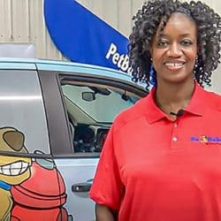 Mary Lester Pet Butler owner in uniform in front of work vehicle