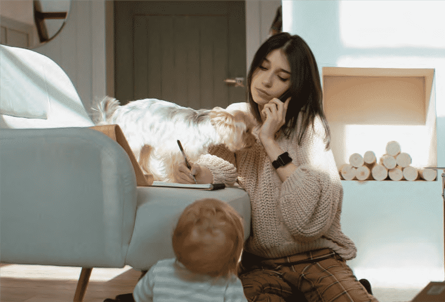 woman working from home with child and dog nearby