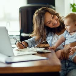 A woman holding her baby while working on a laptop
