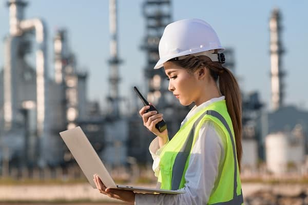 Woman on an energy industry site, looking at her laptop while wearing a hardhat