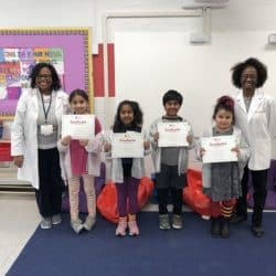 LMS Keena's standing alonside four kindergarden students and another female teacher. Bith teachers wearing lab coats. Children holding completion certificates in hands.