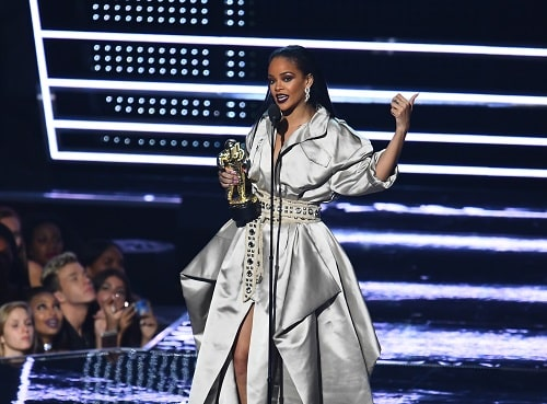 Rihanna accepts an award onstage at MTV event