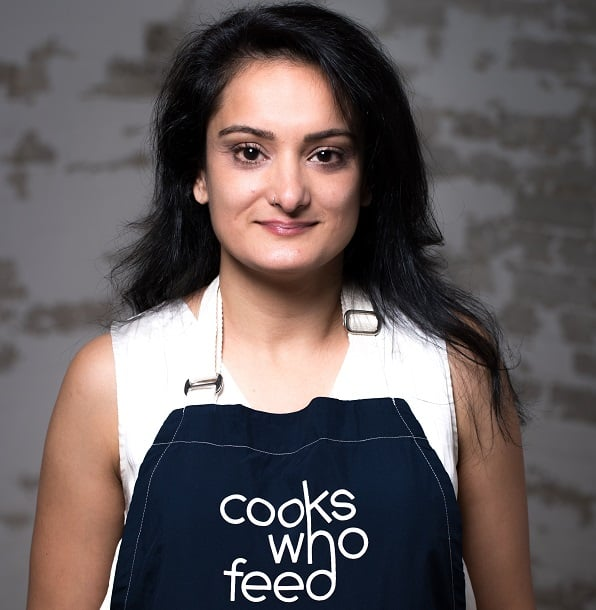 woman wearing a blue apron that says Cooks Who Feed