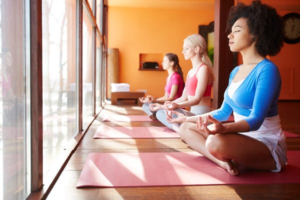 Side view of diverse confident women meditating together on yoga mats sitting near window in sunlight and relaxing