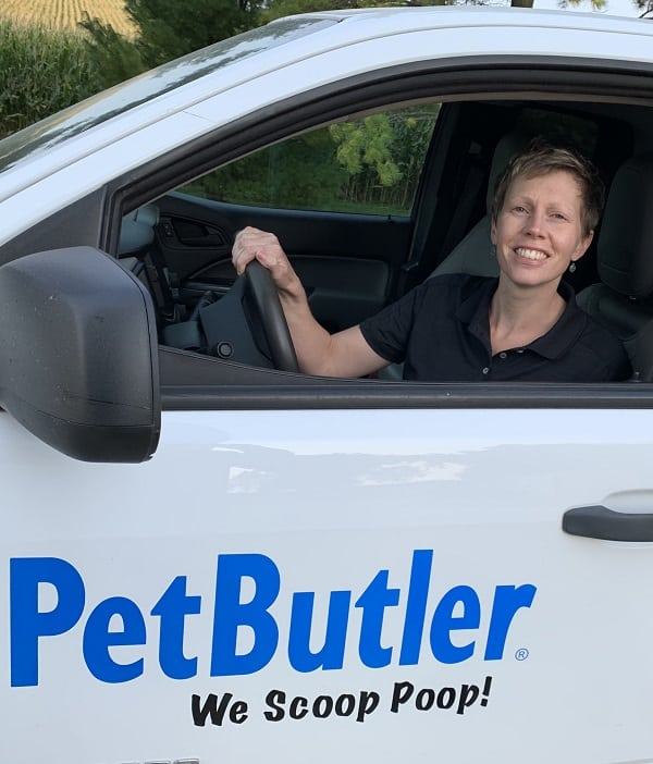 Kelly Amundson sitting behind the wheel of her Pet Butler work vehicle that says We Scoop Poop