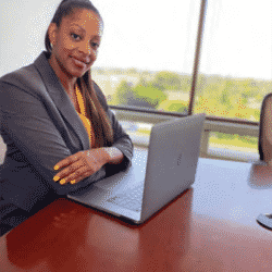 Mika Hilaire seaed at desk in professional attire with laptop open smiling