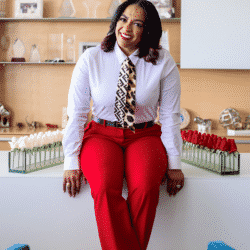 Necole seated on office desk smiling
