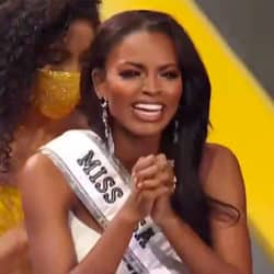 Miss USA pageant winner Asya Branch smilign with sash on and clasping hands