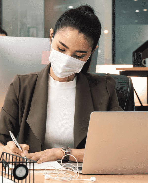 professional woman wearing a mask on her computer at home
