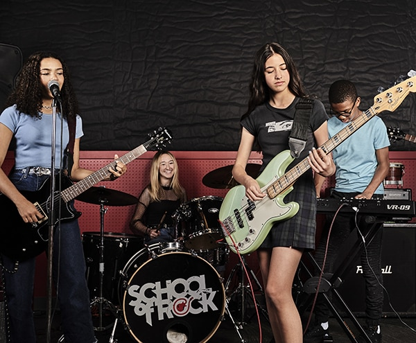 group of diverse music students in school playing guitars and drums