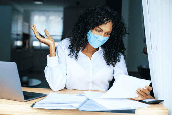 businesswoman-reviewing finances at desk with calculator and wearing a protective mask