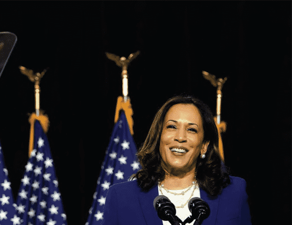 Vice President elect Kamala Harris stands behind podium smiling with U.S. flags int he background