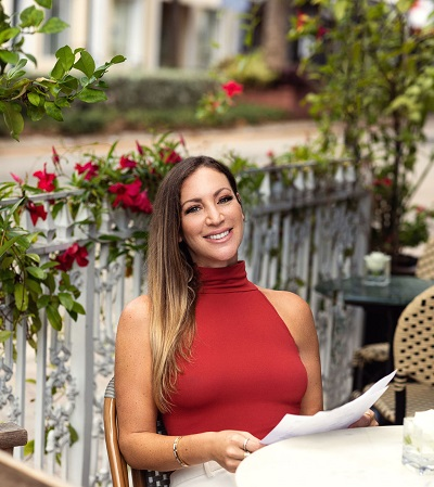 katie sandler is smiling seated at outdoor table holding book in hands