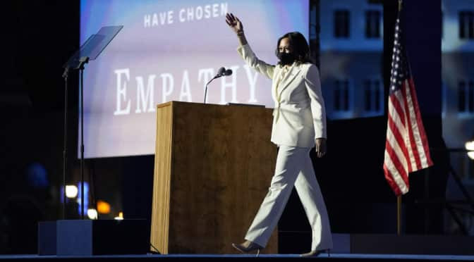 Kamala Harris on stage white suit wearing a mask with flag in background