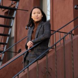 Asian woman standing on stairs wearing a grey suit