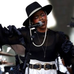 Lauryn Hill singing on stage wearing a black hat with pearls