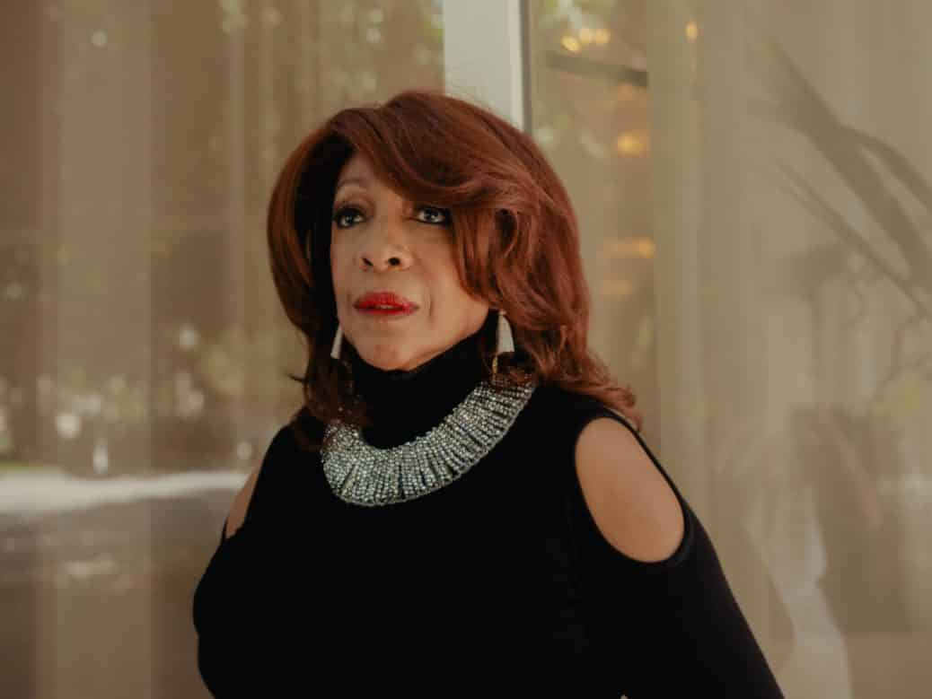 Mary Wilson wearing a black dress, red lipstick and a necklace