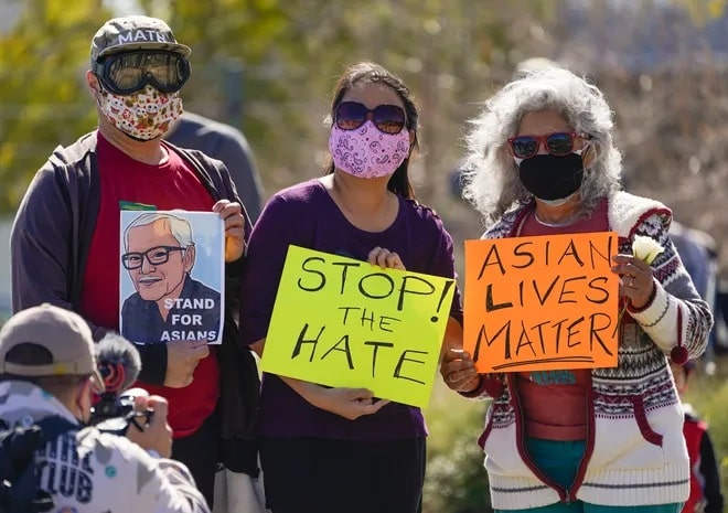 three people stand together holding signs that read stop the hate and Asian lives matter