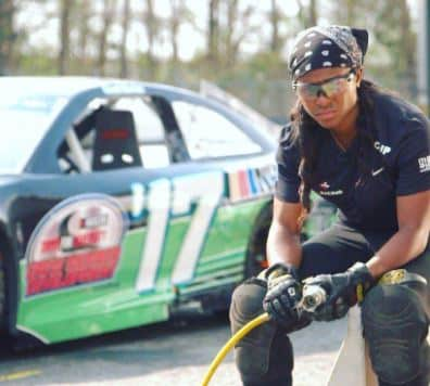 Brehanna Daniels seated wearing a bandana on her head and safety goggles while holding a tire changing hose in front of a NASCAR vehicle.