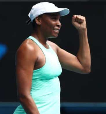 Venus Williams holding her fist up in victory while holding a tennis racket