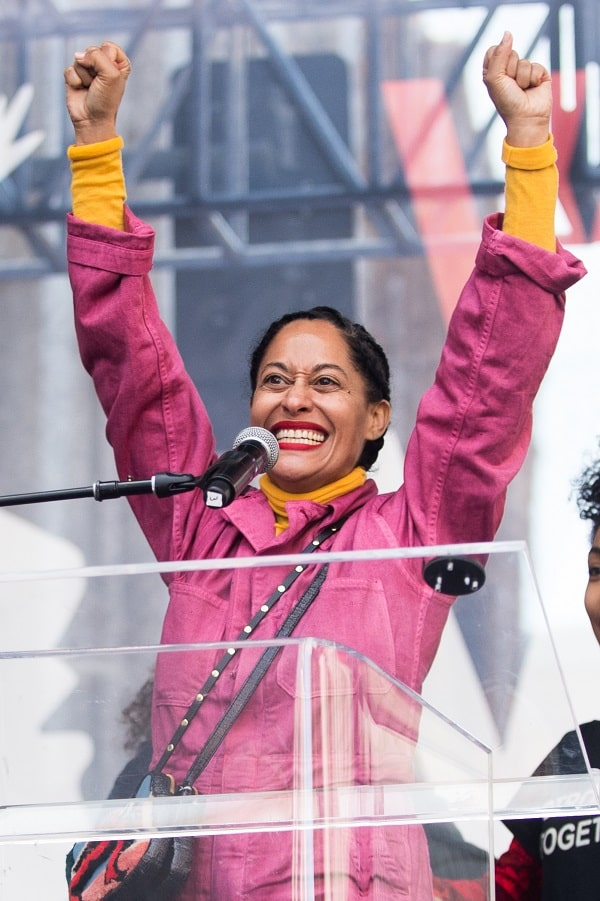 Tracee Ellis Ross standing behind a podium wearing a bright pink jacket smiling with arms raised high in a support gesture