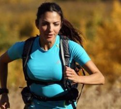 Norma Bastidas running outdoors with a backpack on