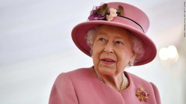 Queen Elizabeth wearing an all pink dress suit and a pink hat while looking away from the camera
