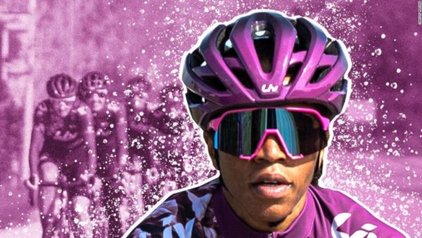 Ayesha McGowan wearing a purple helmet and purple glasses for cycling in front of a purple graphic of cyclists