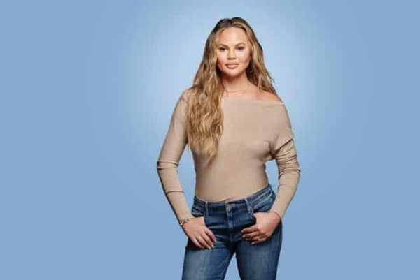 Crissy Teigan standing in front of an all blue back drop posting for the camera with her hands in her blue jean pockets