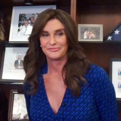 Cailtlyn Jenner in blue dress smiling in front of bookshelf with books and photos