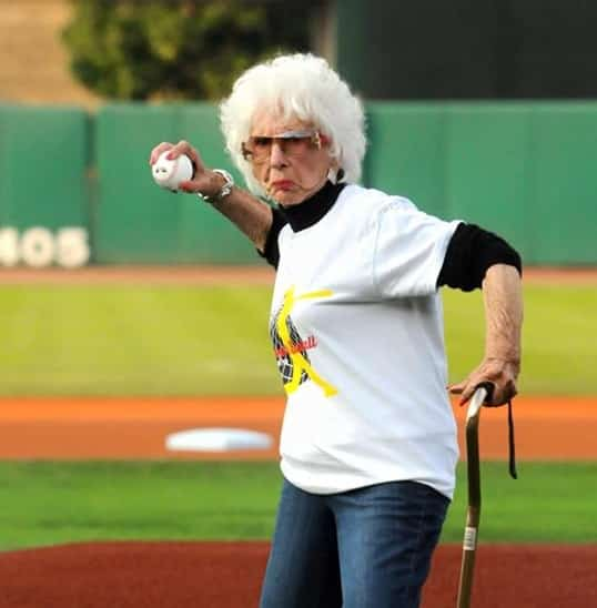An elderly woman with a cane in hand prepares to through a baseball with a stern face.