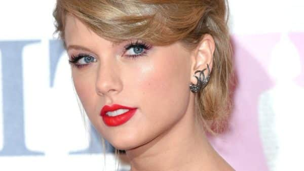Taylor Swift pictured wearing red lips while looking at the camera with her hair up